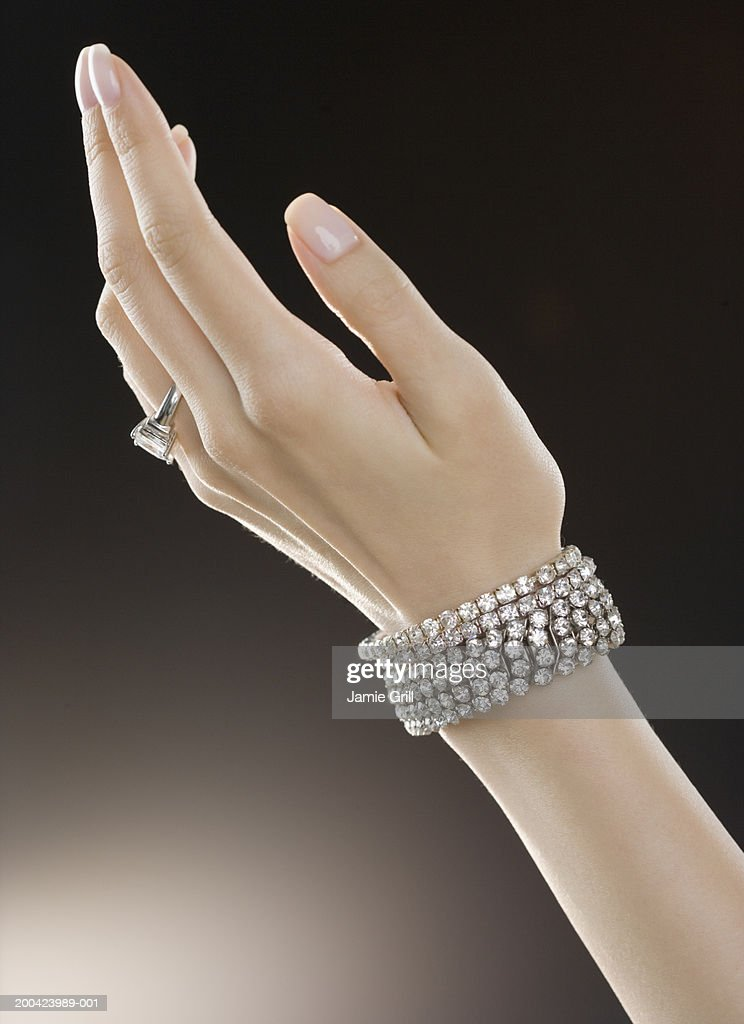Woman wearing diamond ring and bracelets, close-up