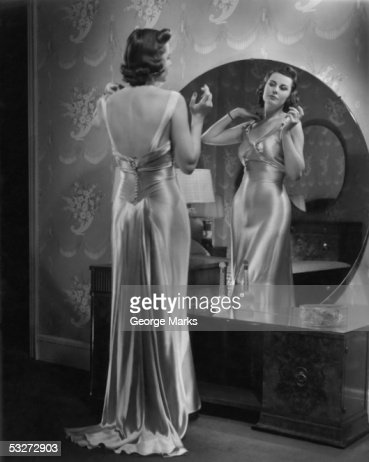 Woman wearing dress looking in mirror : Stock Photo
