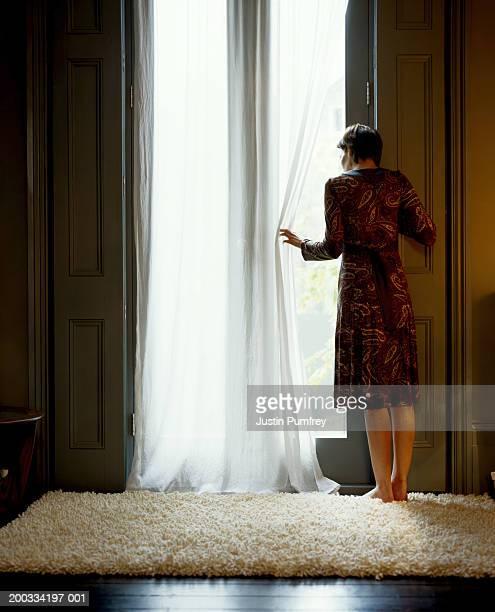Woman wearing dress, looking out window