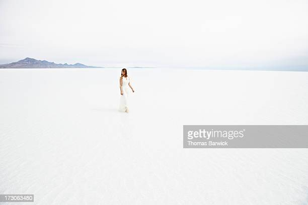 Woman wearing dress walking through shallow water