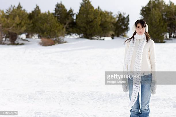 Woman wearing earmuffs in the snow