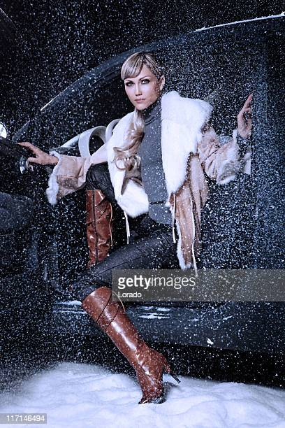 woman wearing elegance boots sitting in car at winter time