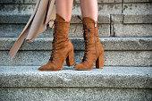 Woman standing on stairs ooutdoor in high heel boots