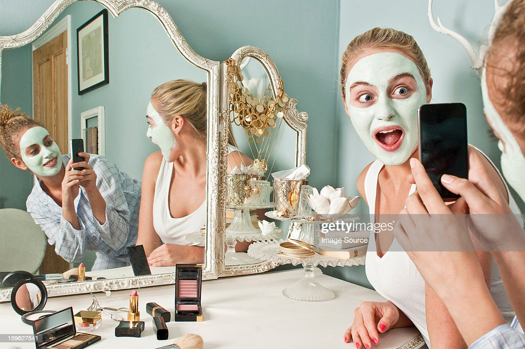 Woman wearing face mask being photographed by friend : Stock Photo