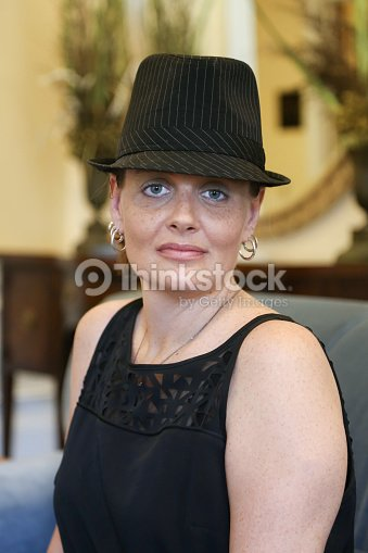 cda94a42 Woman Wearing Fedora Hat Poses For Camera Stock Photo - Thinkstock