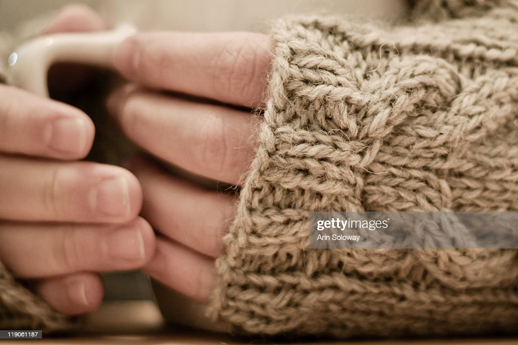 Woman wearing fingerless gloves and holding mug