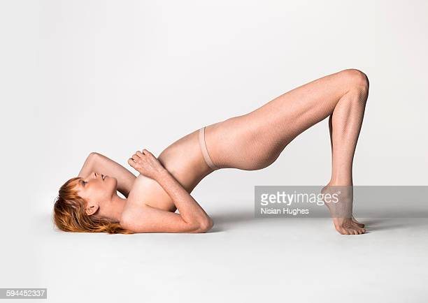 woman wearing fishnet tights on floor arching back