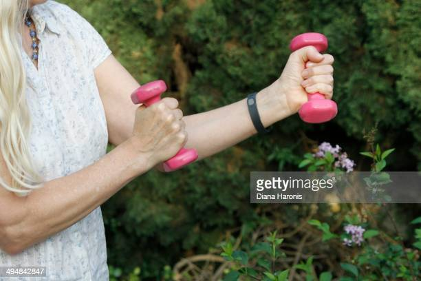 Woman wearing Fitbit and holding weights