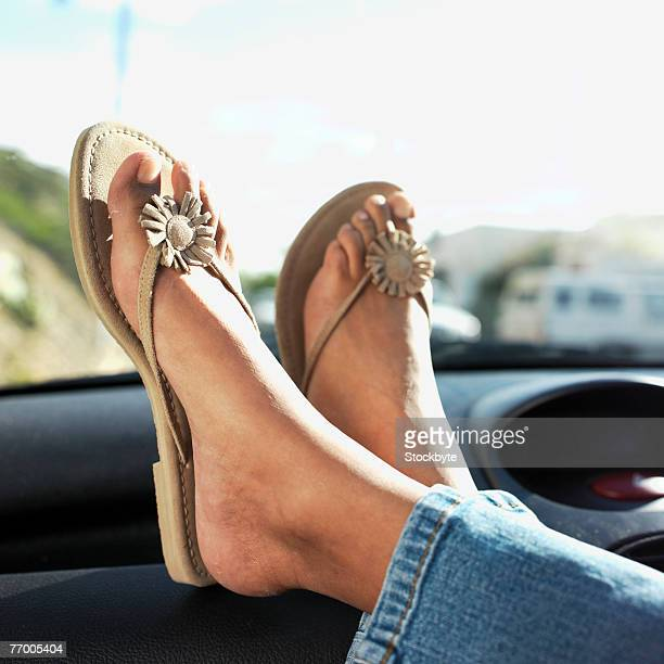 Woman wearing flip flops, sitting with feet up on dashboard in car, low section