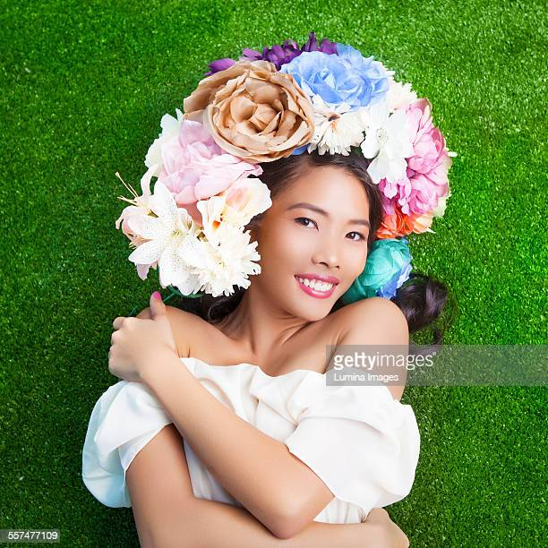 Woman wearing flower crown on artificial grass