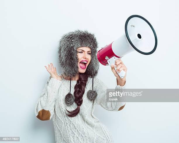 Frau mit Pelz Mütze und Pullover schreien auf Megafon