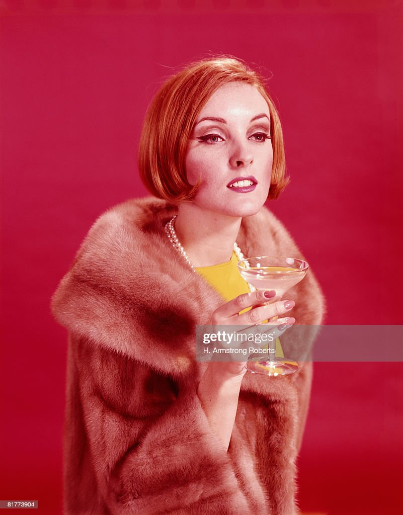 Woman wearing fur coat, holding glass of champagne. (Photo by H. Armstrong Roberts/Retrofile/Getty Images) : Stock Photo