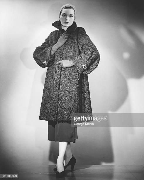 Woman wearing fur coat posing in studio (B&W)