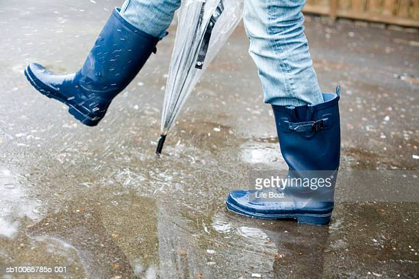 Woman wearing galoshes walking in rain, low section