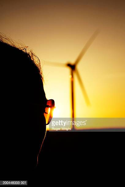 Woman wearing glasses, windmill in background, close-up, backlit
