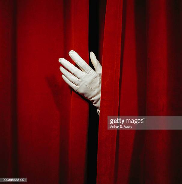 Woman wearing glove, parting curtain