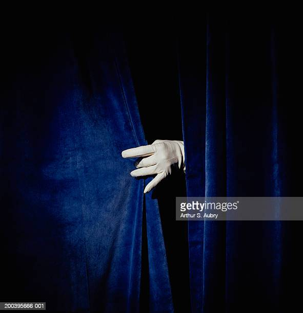 Woman wearing glove, pulling curtain shut