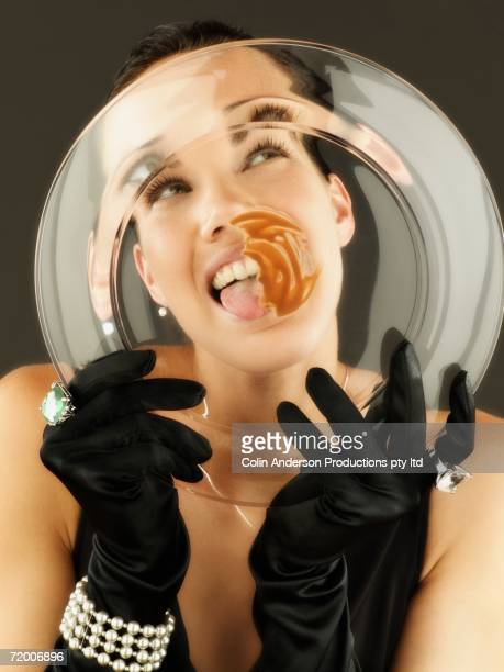Woman wearing gloves and jewels licking plate