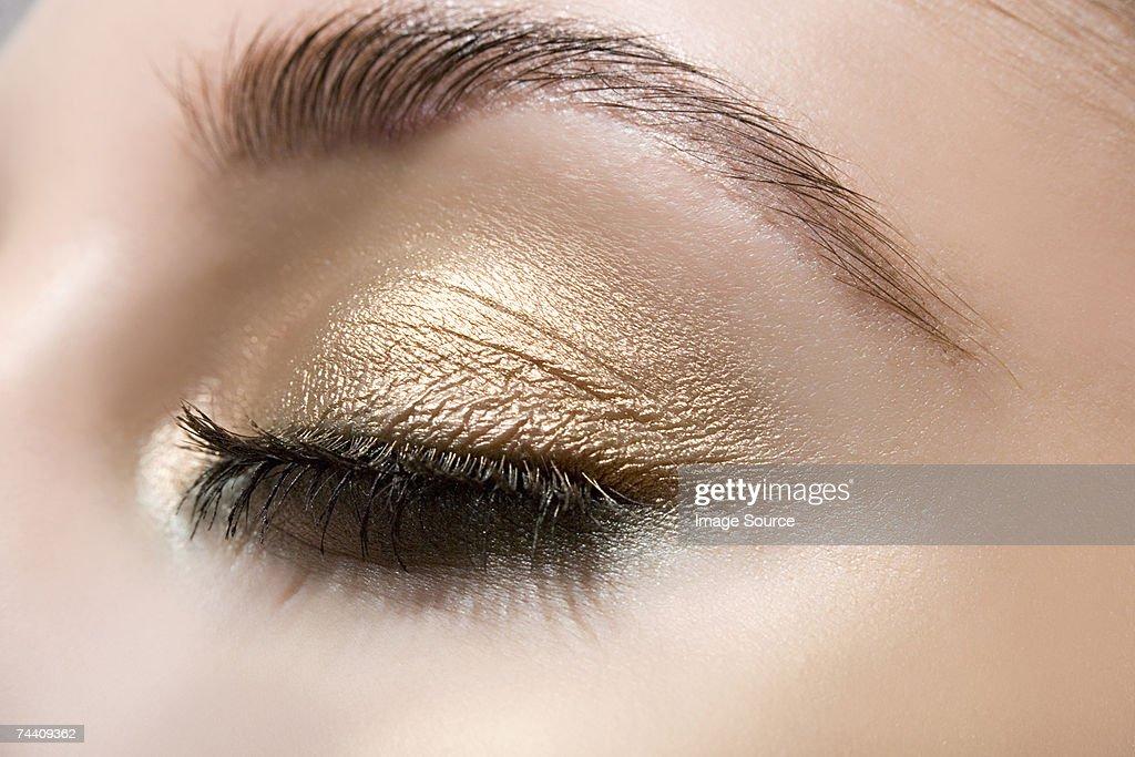 Woman wearing gold eye shadow : Stock Photo