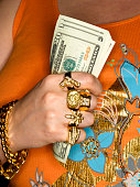 Woman wearing gold jewellery, holding US dollar banknotes, mid section