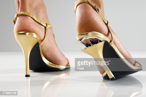 Woman Wearing Gold Shoes with Broken Heel