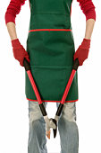 Woman wearing green apron holding branch cutters, mid section