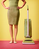 Woman wearing green outfit standing next to green vacuum