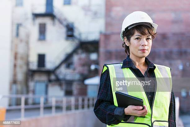 Woman wearing hard hat holding digital tablet