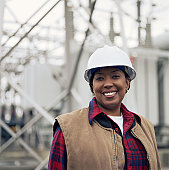 Woman wearing hard hat in front of power station, portrait