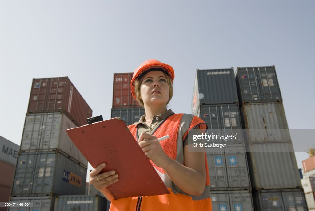Woman wearing hard hat standing by shipping containers with clipboard : Stock Photo