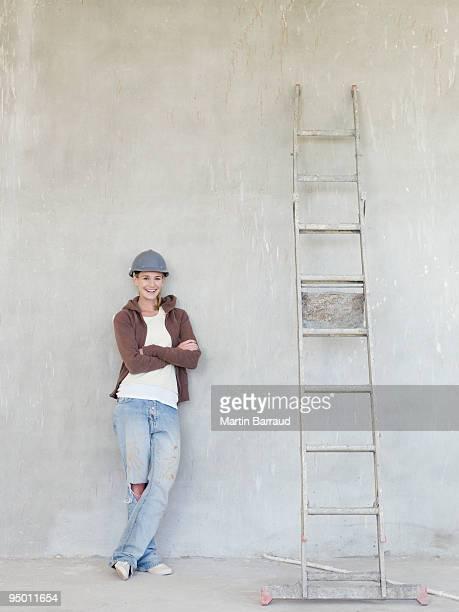 Frau mit harten-Hut und an die Wand gelehnt mit Leiter
