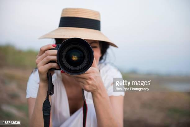 Woman wearing hat taking photograph