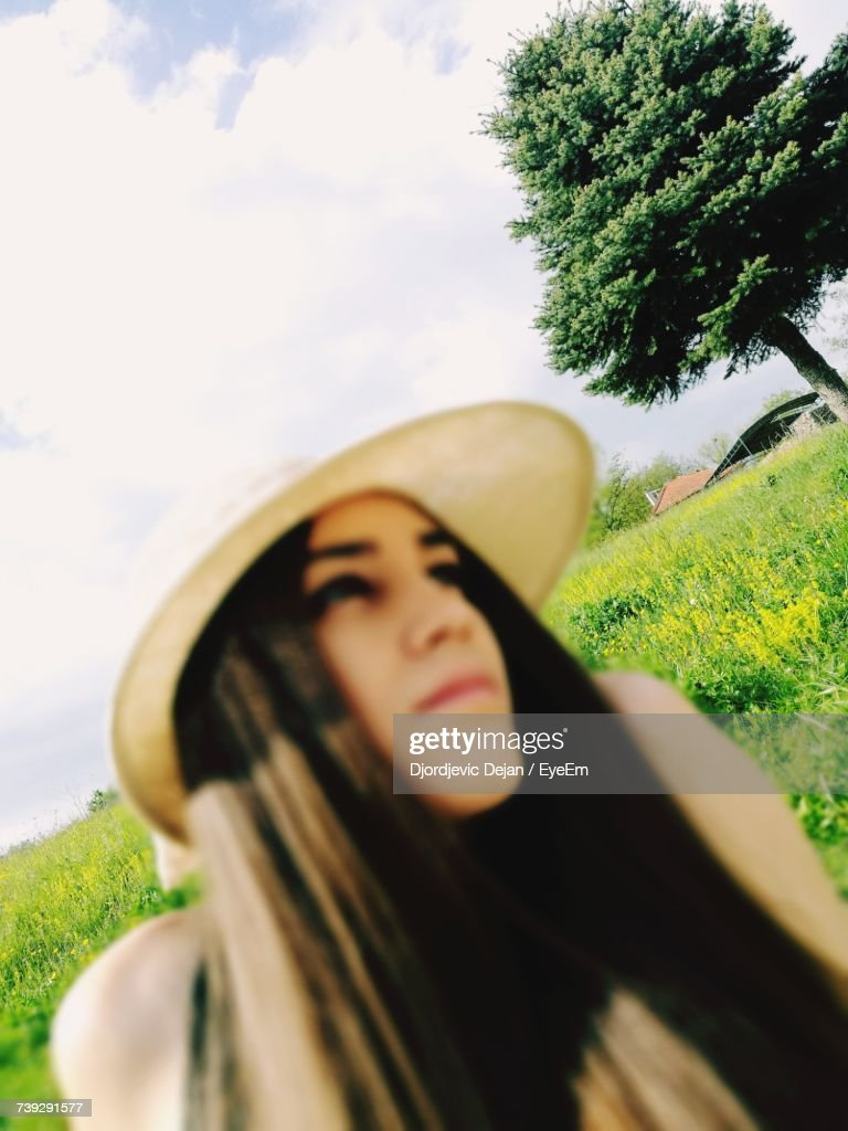Woman Wearing Hat While Looking Away Against Sky : Stock Photo