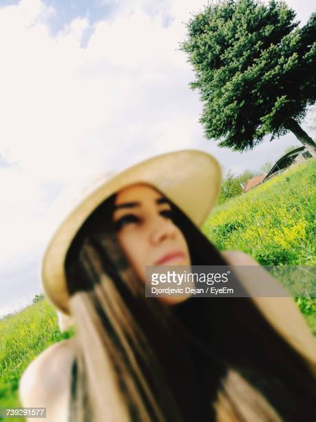 Woman Wearing Hat While Looking Away Against Sky