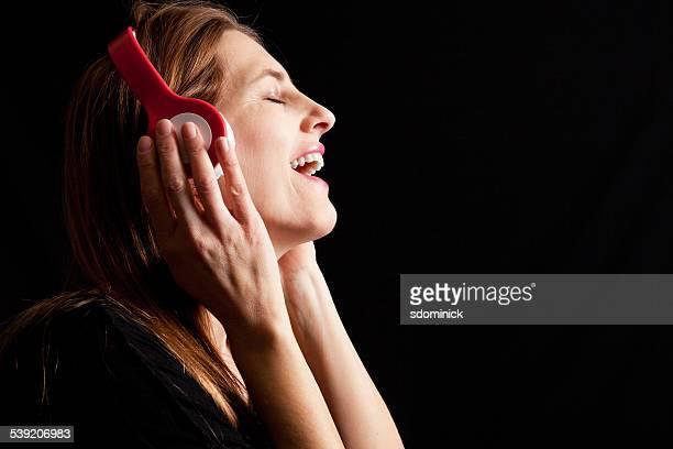 Femme portant des écouteurs et de chants de la musique