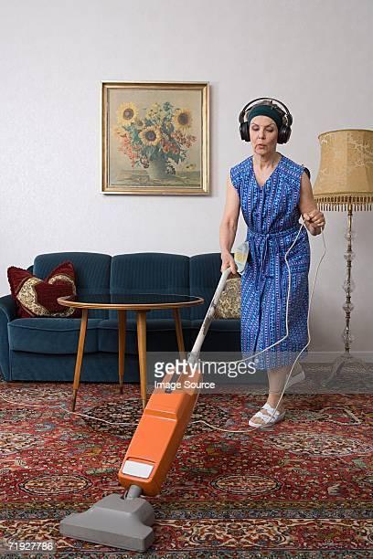 Woman wearing headphones and vacuuming