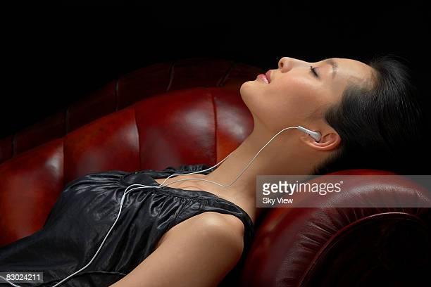 Woman wearing headphones, eyes closed