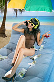 Cheerful woman wearing headphones and with mobile phone and money on the beach