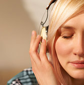 Woman wearing headphones with eyes closed.