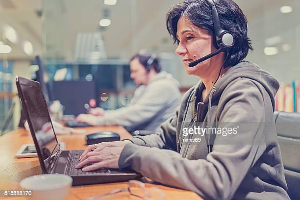 Mujer usando auriculares en computadora habitación