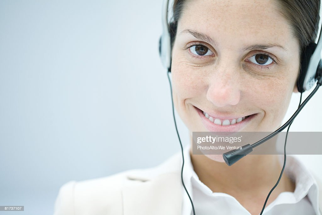 Woman wearing headset, smiling at camera