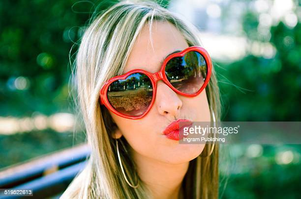 Woman wearing heart shaped glasses puckering in park