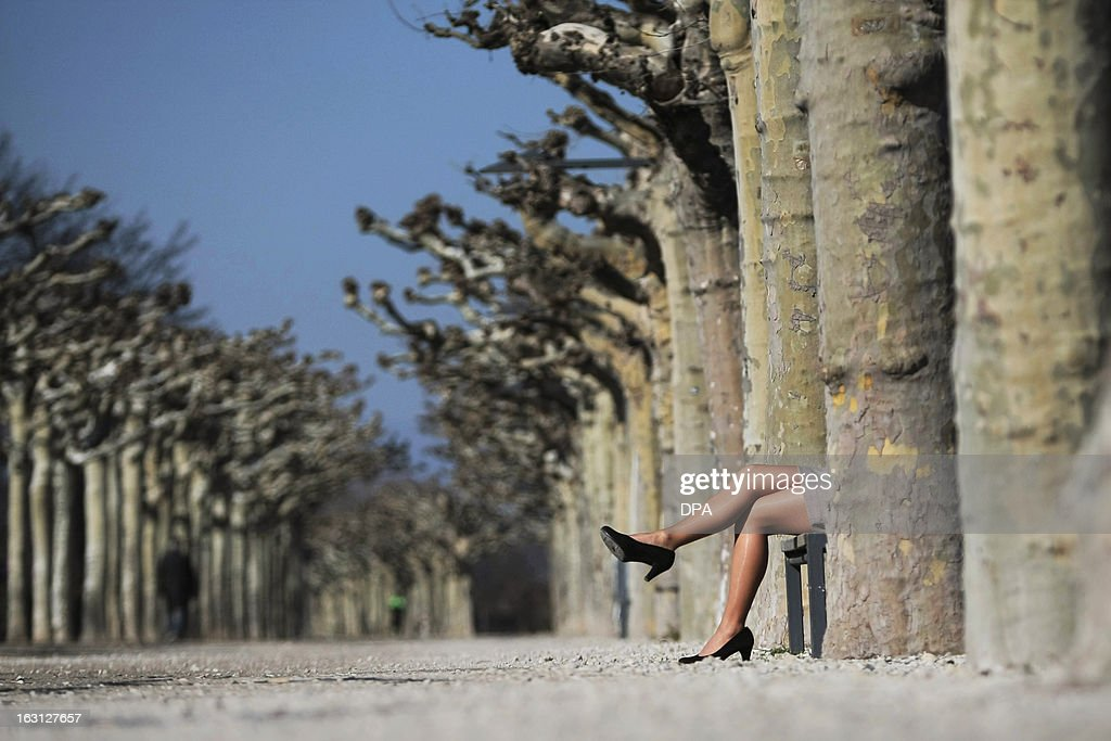 A woman wearing high heels, nylon stockings and a skirt sits on a park bench and enjoys the sunny spring day in Mainz, western Germany on March 5, 2013.
