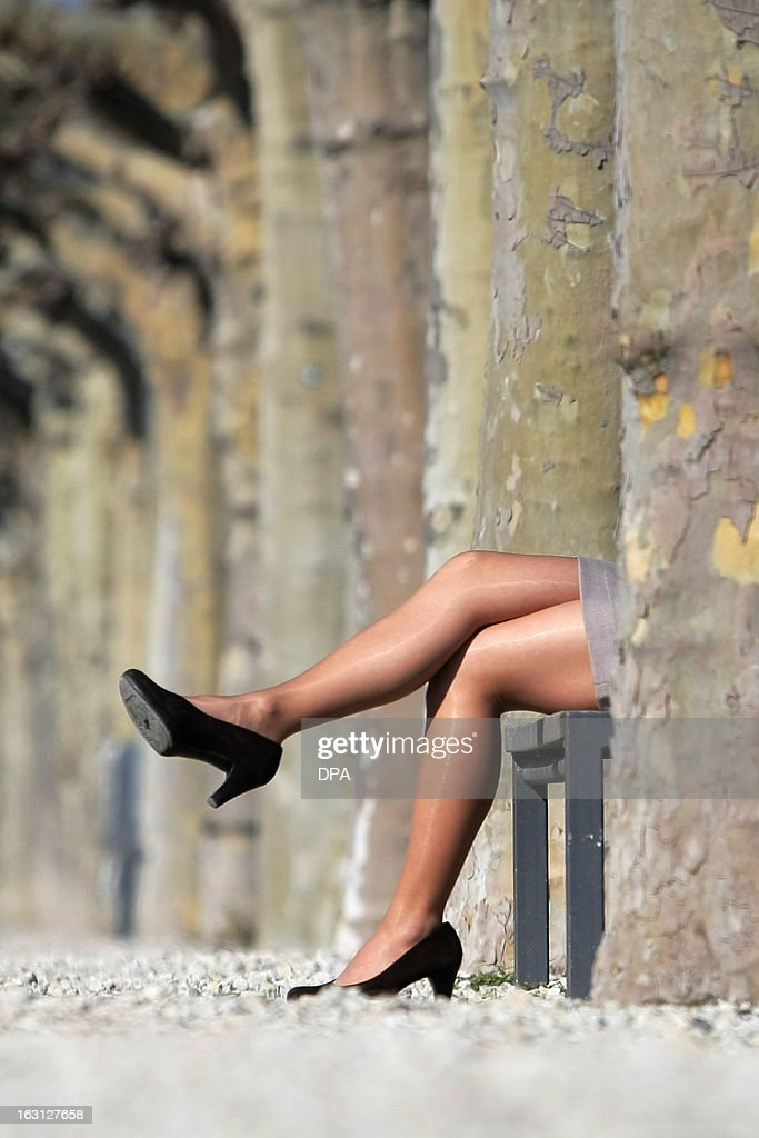 A woman wearing high heels, nylon stockings and a skirt sits on a park bench and enjoys the sunny spring day in Mainz, western Germany on March 5, 2013. AFP PHOTO / FREDRIK VON ERICHSEN GERMANY OUT