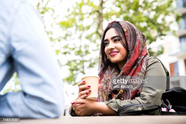 Woman wearing hijab enjoying coffee with friend