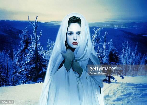 Woman wearing hooded cape in winter landscape (digital composite)