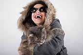 Woman wearing hooded coat, holding cat, laughing