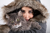 Woman wearing hooded coat, holding cat, portrait, close-up