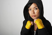 Woman wearing hooded robe with boxing wraps, portrait