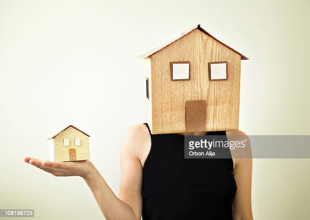 Woman Wearing House as Mask Holding Smaller, Similiar Home